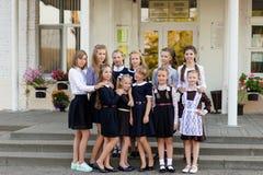 一个小组校服的女小学生面对学校 免版税库存图片
