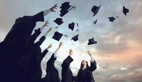 一个小组毕业生投掷帽子入天空 库存照片