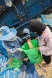 一个小组泰国农夫使用一个机器分离米仁, 库存照片
