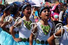 一个小组狂欢节舞蹈家以各种各样的服装在沿街道的欢欣跳舞 免版税库存图片