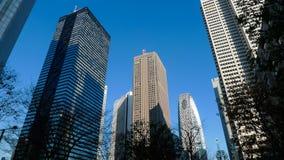 一个小组现代摩天大楼在有美丽的天空和云彩的东京市 库存图片