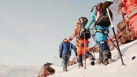 一个小组登山人通过密集的雪互相跟随,最后游人的腿属于雪 在他们的右边 股票视频