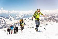 一个小组登山家在一座积雪覆盖的山的上面上升 免版税库存图片