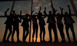 一个小组的剪影举他们的手的商人 免版税图库摄影