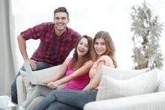 一个小组的画象青年人坐长沙发在客厅 库存照片