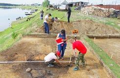 一个小组科学家在西伯利亚村庄举办考古学挖掘 免版税库存照片