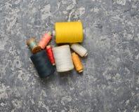 一个小组螺纹多彩多姿的丝球在灰色具体背景的 针线的概念 做的手缝合的衣裳 免版税库存照片
