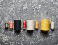 一个小组螺纹多彩多姿的丝球在灰色具体背景的 针线的概念 做的手缝合的衣裳 库存图片