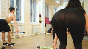 一个小组运动员参与用一根体操棍子健身房 影视素材