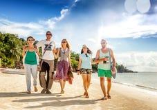 一个小组青年人朋友30年在海滩, happ走 库存照片