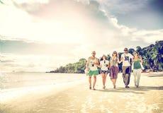 一个小组青年人朋友30年在海滩, happ走 库存图片