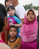 一个小组马来西亚孩子看人分布的小鱼苗 免版税图库摄影