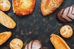 一个小组黑暗的土气表面,您的文本的一个地方上的各种各样的面包 新鲜面包框架  在视图之上 库存图片
