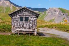 一个小经济房子,位于瑞士阿尔卑斯,包围由一个美好的山风景 免版税库存照片