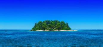 一个小绿色海岛在风平浪静 库存照片
