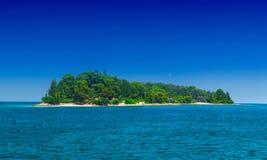 一个小绿色海岛在风平浪静 库存图片