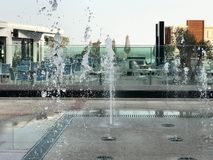 一个小美丽的唱歌喷泉露天,在街道上 水滴,在fligh的天空中结冰的水喷气机 免版税库存图片
