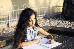 一个小美丽的女孩在公园画心脏 免版税库存图片