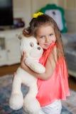 一个小美丽的女孩拥抱滑稽的熊 库存照片