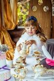 一个小美丽的女孩的正面图阿丽斯风景的妙境倾吐的茶的到一个杯子里在桌上 免版税库存图片