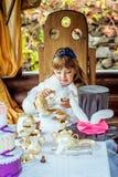一个小美丽的女孩的正面图阿丽斯风景的妙境倾吐的茶的到一个杯子里在桌上 库存照片