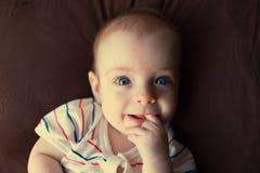 一个小蓝眼睛的男孩的画象,在床上在她的嘴躺并且投入她的手指 图库摄影