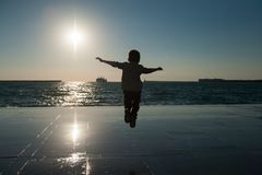一个小跳跃的男孩的剪影海日落背景的与一艘船的在天际 免版税库存图片