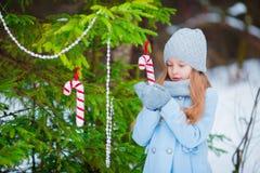 一个小逗人喜爱的微笑的女孩的画象站立在冷淡的装饰的圣诞树附近的一件蓝色外套和手套的 免版税库存照片