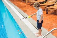 一个小逗人喜爱的男孩抓在水池的一条玩具鱼 免版税库存照片