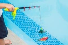 一个小逗人喜爱的男孩抓在水池的一条玩具鱼 库存图片