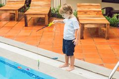 一个小逗人喜爱的男孩抓在水池的一条玩具鱼 库存照片