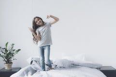 一个小黑发女孩在与一个智能手机的床上跳舞在她的手和耳机上 图库摄影