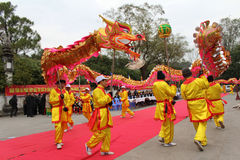 一个小组亚裔人民跳舞在民间节日的龙 库存图片