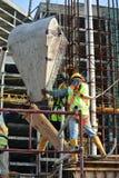 一个小组倾吐混凝土的建筑工人入专栏形式工作 免版税库存照片