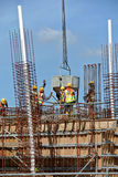 一个小组倾吐混凝土的建筑工人入地梁形式工作 免版税库存图片