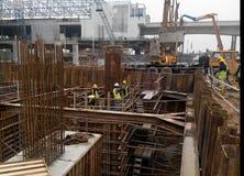 一个小组倾吐混凝土的建筑工人入桩帽模板 库存照片