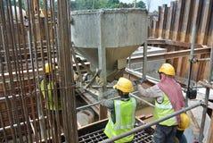 一个小组倾吐混凝土的建筑工人入桩帽模板 免版税库存图片