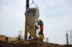 一个小组倾吐混凝土的建筑工人入模板 免版税图库摄影