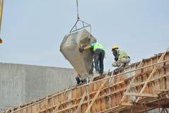 一个小组倾吐混凝土的建筑工人入模板 库存照片