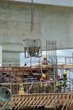 一个小组倾吐混凝土的建筑工人入水泥板形式工作 免版税图库摄影