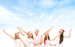 一个小组圣诞节帽子posin的愉快和情感少年 免版税库存照片