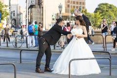 一个小组在布达佩斯街道上的婚礼摄影师举行两三个新婚佳偶的一场照相讲席会 免版税库存图片
