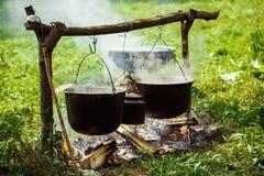 一个小组大锅和水壶垂悬在火 库存照片