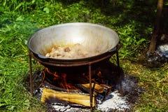 一个小组大锅和水壶垂悬在火 免版税库存照片