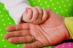 一个小婴孩的手母亲的 库存照片