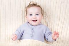 一个小婴孩的画象在一条温暖的被编织的毯子下的 库存图片