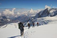一个小组登山人下降对营地,帕米尔 库存照片