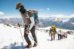 一个小组登山家在一座积雪覆盖的山的上面上升 免版税库存照片