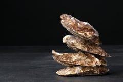 一个小组新近地和在黑背景的未加工的被去外皮的牡蛎 变冷的未加工的牡蛎 可口热带海软体动物 库存照片