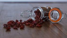从一个小玻璃瓶子出来的小goji莓果 免版税库存图片